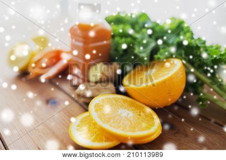 healthy eating, food, diet and vegetarian concept - close up of orange, bottle with carrot juice and vegetables on wooden table over snow
