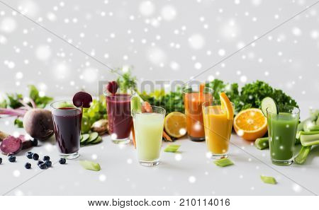 healthy eating, drinks, diet and detox concept - glasses with different fruit or vegetable juices and food on table over snow