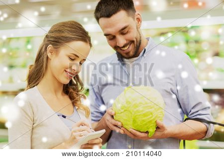 shopping, food, sale, consumerism and people concept - happy young couple with basket and notebook buying cabbage at grocery store or supermarket over snow