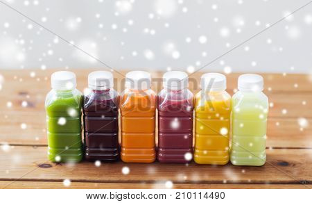 healthy eating, drinks, diet and packaging concept - plastic bottles with different fruit or vegetable juices on wooden table over snow