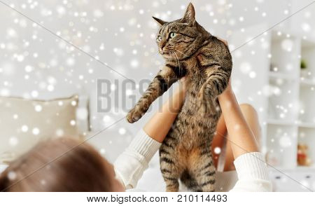 pets, winter and people concept - young woman with cat lying in bed at home over snow