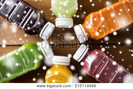 healthy eating, drinks, diet and packaging concept - close up of plastic bottles with different fruit or vegetable juices on wooden table over snow