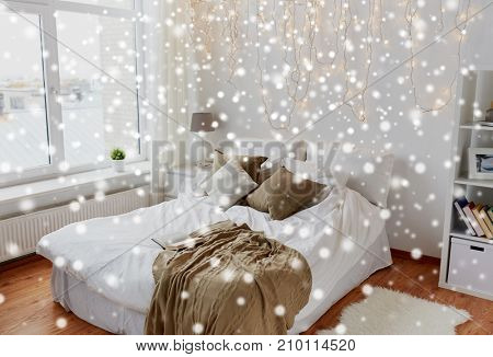 cosy home, interior and holidays concept - cozy bedroom with bed and christmas garland lights over snow