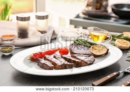 Plate with delicious grilled steaks on kitchen table