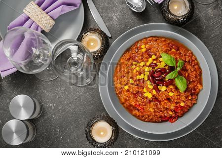 Bowl with delicious chili con carne on served table