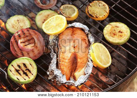 Tasty salmon steak with vegetables on barbecue grill, close up