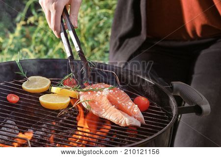 Woman cooking salmon steak on barbecue grill outdoors