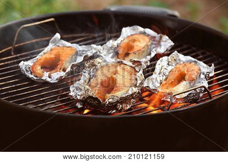 Tasty salmon steaks on barbecue grill, close up