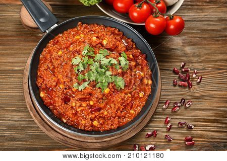 Frying pan with delicious chili con carne on wooden background