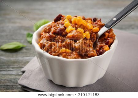 Bowl with chili con carne on table