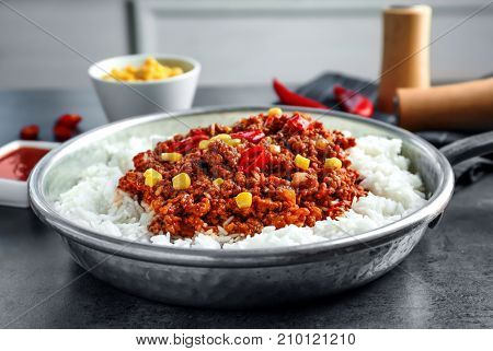 Saucepan with chili con carne and rice on table