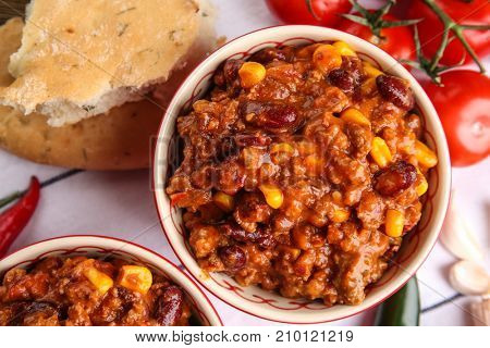 Composition with chili con carne in bowls on table, closeup