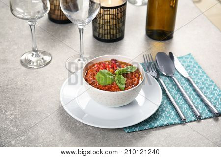 Served table with delicious chili con carne in bowl