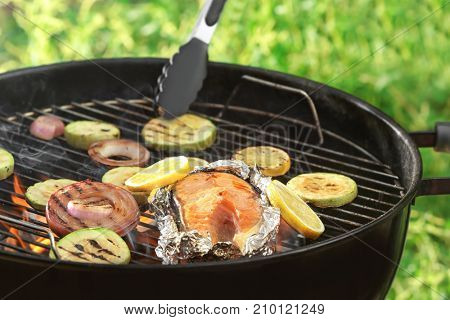 Cooking of tasty salmon steak with vegetables on barbecue grill outdoors