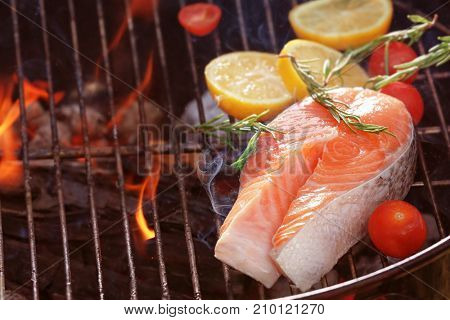 Salmon steak with lemon and rosemary on barbecue grill, close up