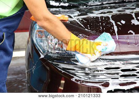 Man washing automobile hood with sponge