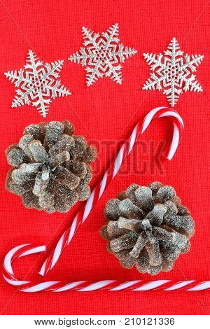 Christmas decorations on textured red background in vertical format shot from overhead