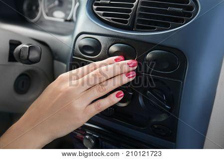 Woman pushing button on dashboard in car