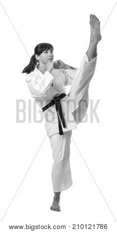 Young woman practising karate on white background