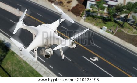 Unmanned Aircraft System (UAV) Quadcopter Drone In The Air Over Roadway.