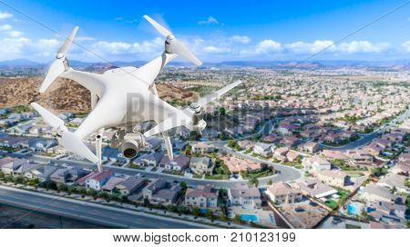 Unmanned Aircraft System (UAV) Quadcopter Drone In The Air Over Residential Neighborhood.