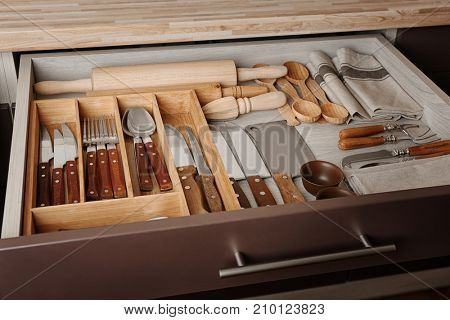 Set of cutlery and kitchen utensils in drawer