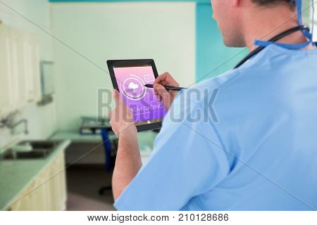 Surgeon using digital tablet  against data loading text with download symbol