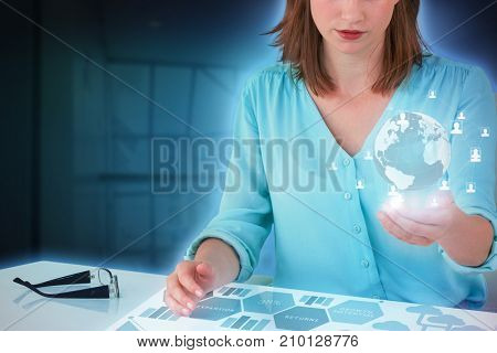 Businesswoman sitting at desk and using digital screen against composite image of graph