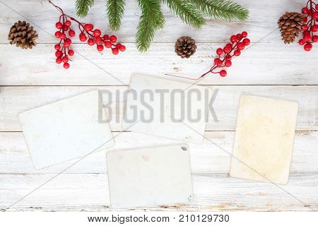 Christmas theme background with blank photo paper and decorating elements on white wood table. Creative Flat layout and top view composition with border and copy space design.