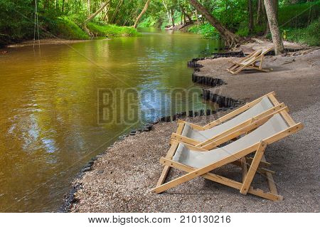 Relaxation Concept : Close up brown wooden bench or armchair on small rocks beside the river with green natural background.