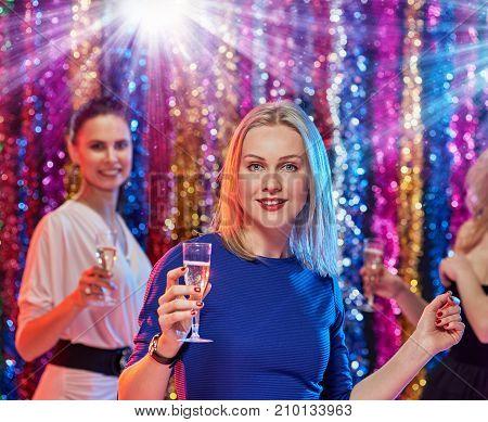 Three beautiful women celebrating new year and drinking champagne
