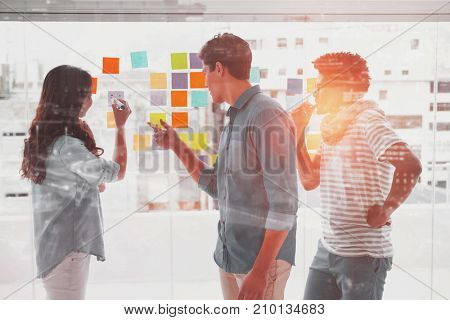 Illuminated cityscape against young creative team writing on adhesive notes