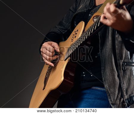 Close up photo of young musician playing on the acoustic guitar