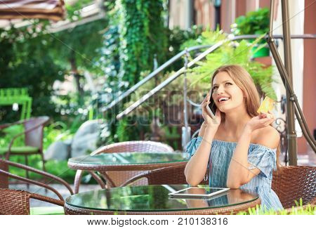 Young woman with cell phone and credit card in cafe