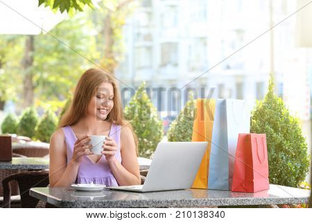 Young woman with laptop in cafe