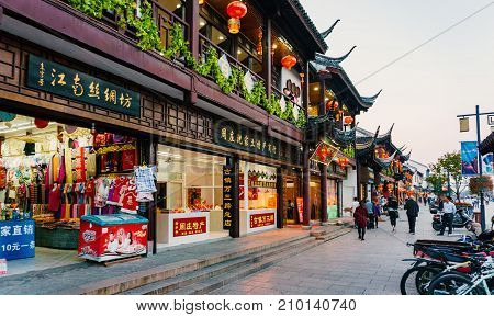 Suzhou, China - Nov 5, 2016: Shopping street at the historic Zhouzhuang Water Town. Numerous visitors can be seen walking along this path.