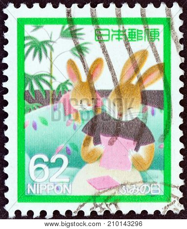 JAPAN - CIRCA 1989: A stamp printed in Japan issued for the letter writing day shows Mother Rabbit reading letter, circa 1989.