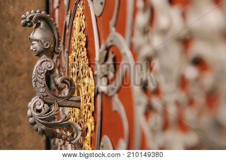 Close-up - decorative element - door handle made in the form of figure of man with mustache on background of red canvas and decorative patterns