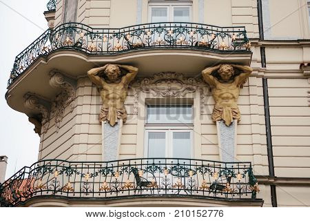 European architecture. Close-up - sculptures - columns in the form of antique characters supporting balcony - facade of vintage historic building. Sculptures- columns in antique style on facade of old building