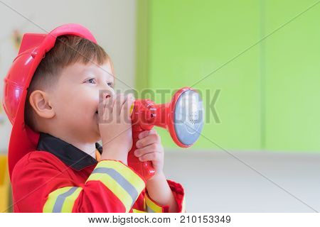 Caucasian boy kid dress up to fireman and use speaker at roll play classroomKindergarten preschool education concept.