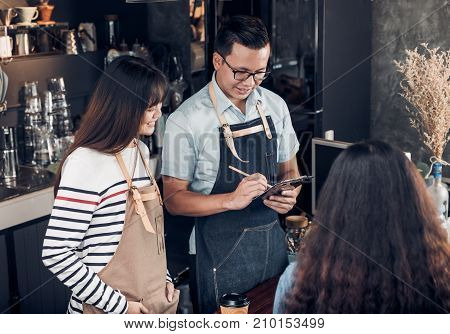 Asia Barista waiter take order from customer in coffee shopTwo cafe owner writing drink order at counter barFood and drink business conceptService mind concept