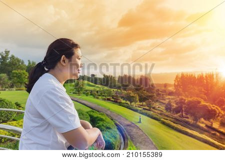 thinking about or missing passed good memory asian women smile looking for the future concept at nature park sunrise sky