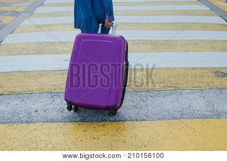 The girl drags a suitcase on wheels in the city on the crosswalk