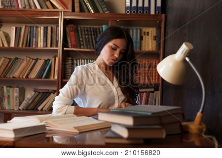 beautiful girl is preparing for the exam reading book at the library