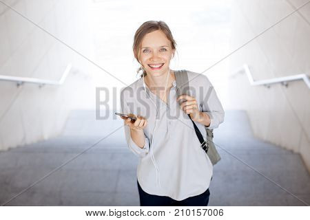 Happy attractive student making video call and looking at camera. Cheerful young businesswoman listening to music in earphones. Lifestyles concept