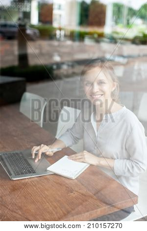 Smiling pretty female manager working in cafe and looking at camera. Happy excited young businesswoman using laptop and writing in notepad. Coworking space concept