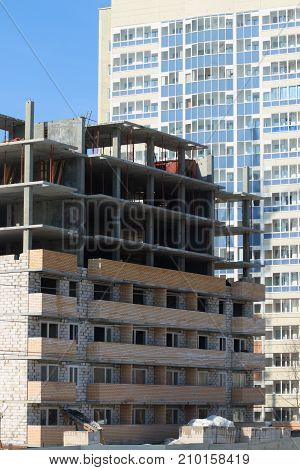 Construction of multi-storey monolithic house and freshly built multi-storey residential building