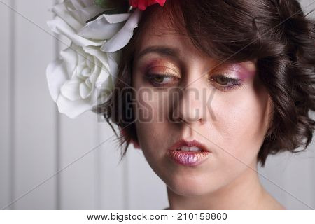 young brunette woman with clean skin make-up and flower wreath in her hair posing at white door closeup looks down