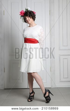 Beautiful young brunette woman in white dress with flower wreath in her hair posing near white door in photo studio