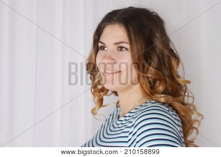 Beautiful young blonde woman with clean skin and make-up posing near white curtains look throw